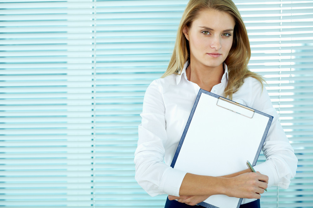 Portrait Of Young Businesswoman With Clipboard Looking At Camera