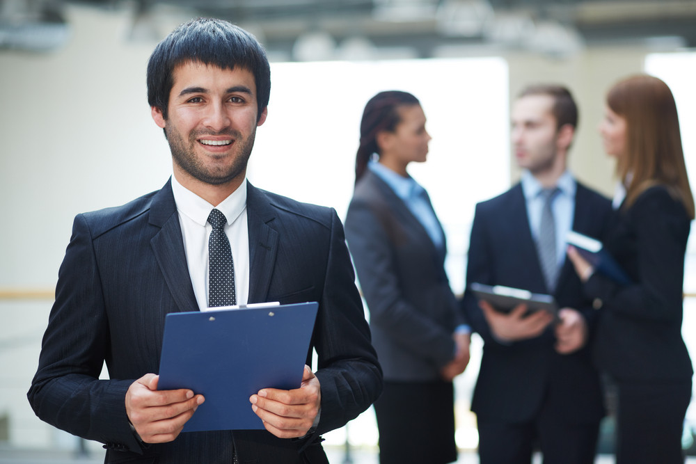 Portrait Of Friendly Male Leader With Document Looking At Camera In Working Environment