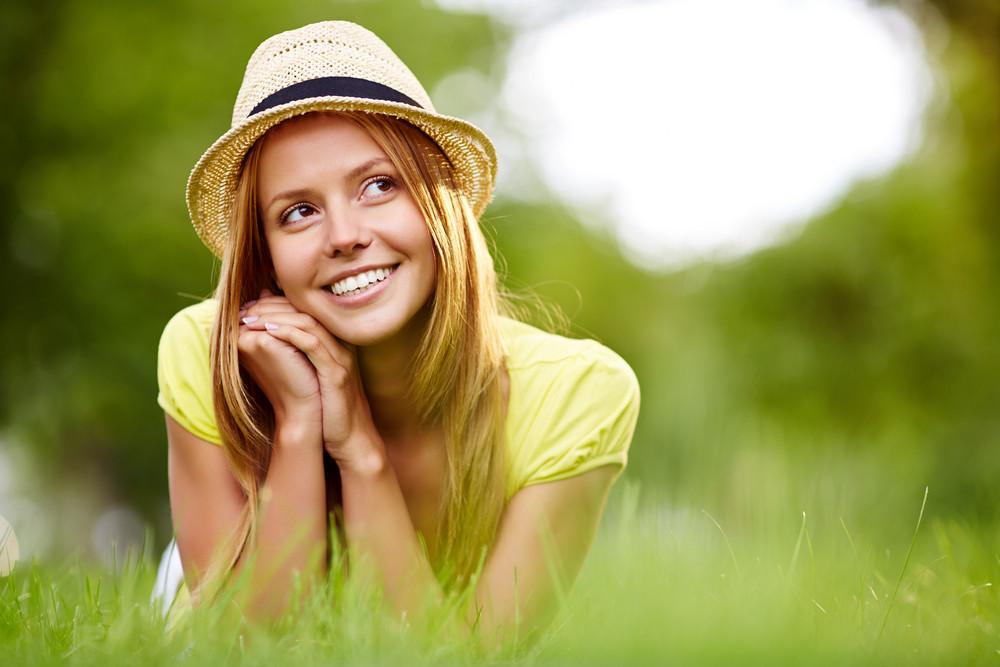 Happy Girl In Hat Lying In Grass In Park