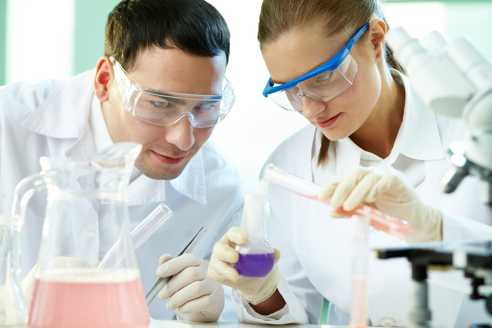 Portrait Of Two Chemists Working With Different Liquids In Tubes