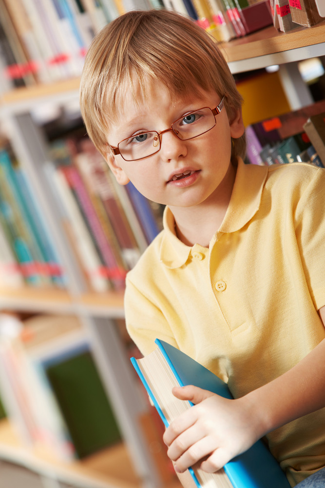 Portrait Of Clever Boy Holding Book And Looking At Camera In Library