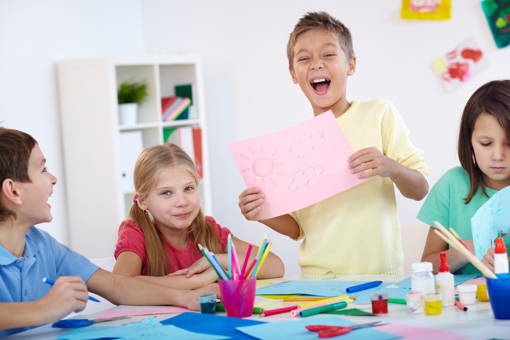 Glad Little Boy Showing His Drawing To His Friends In Classroom