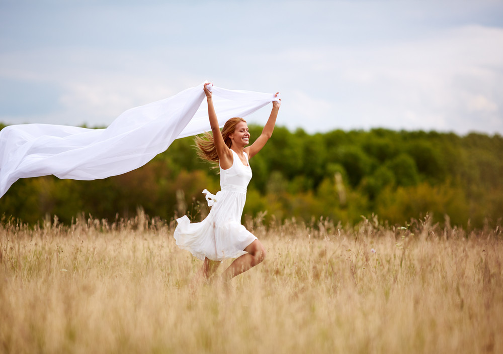 Image Of Happy Woman Holding A White Fabric While Running Down Meadow