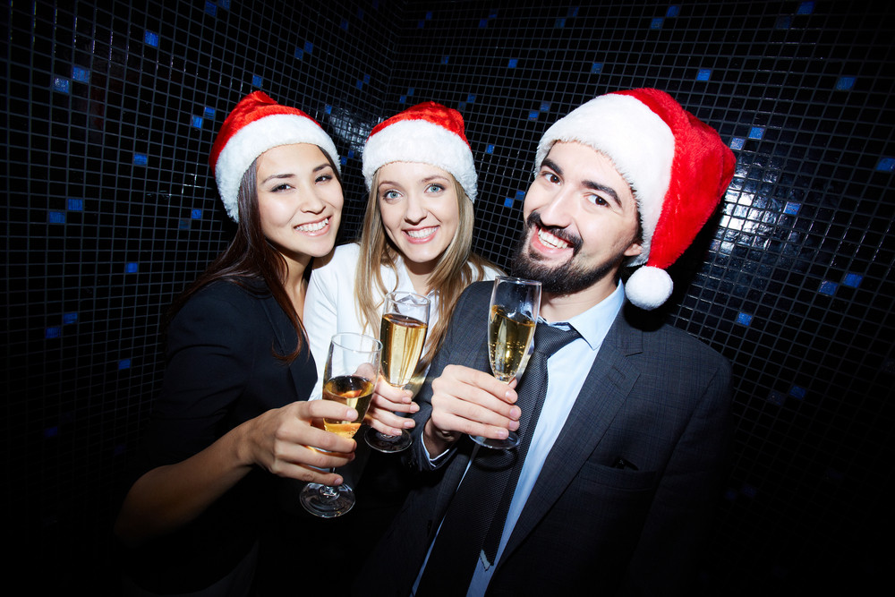 Group Of Cheerful Business People In Santa Caps Toasting With Champagne In Nightclub