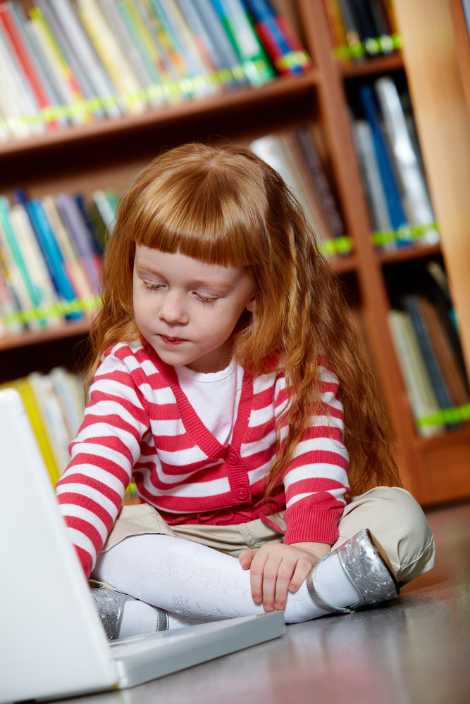 Portrait Of Smart Girl Sitting On The Floor In Library In Front Of Laptop