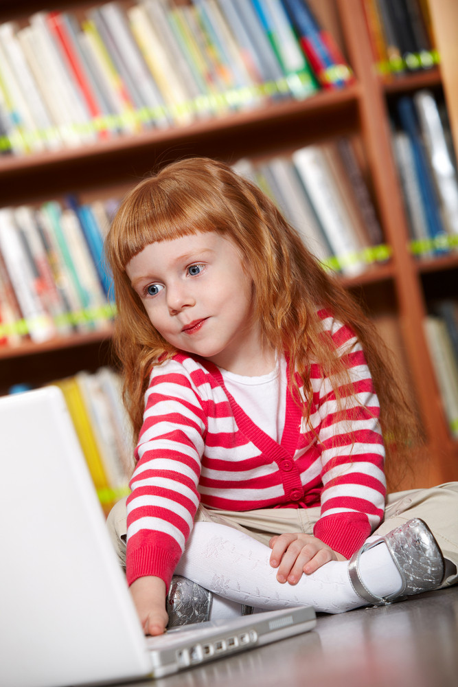 Portrait Of Smart Girl Sitting On The Floor In Library In Front Laptop