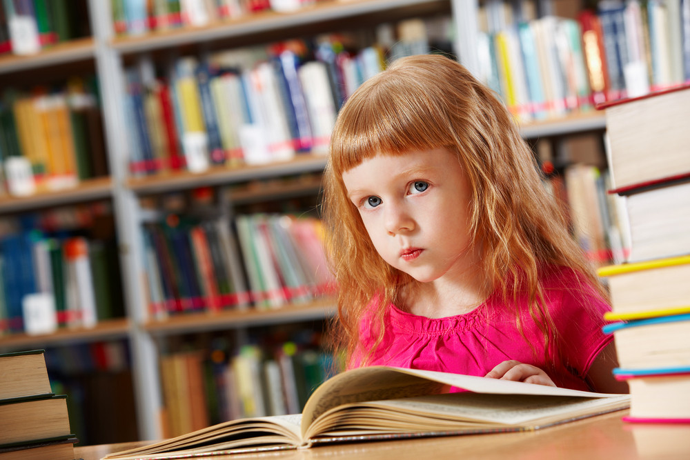 Portrait Of Smart Girl Reading Book In Library