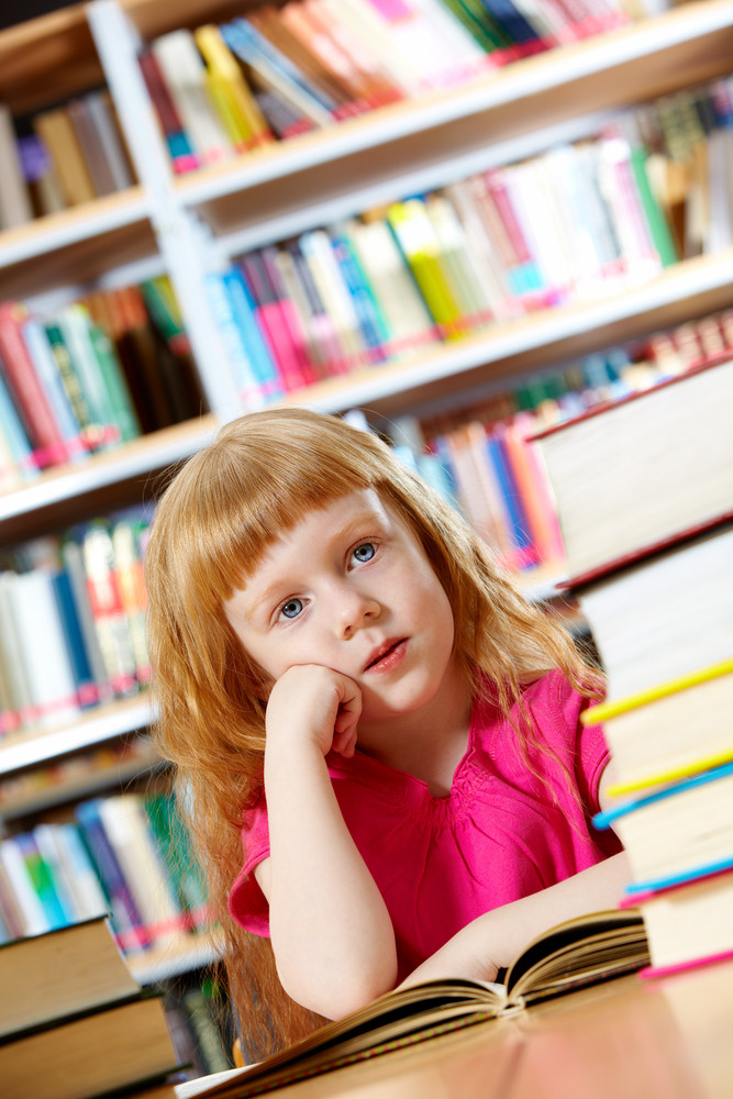 Portrait Of Smart Girl With Book In Library