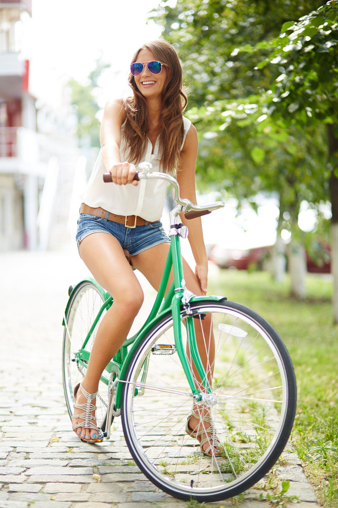 Portrait Of A Pretty Woman On Bicycle In The Park