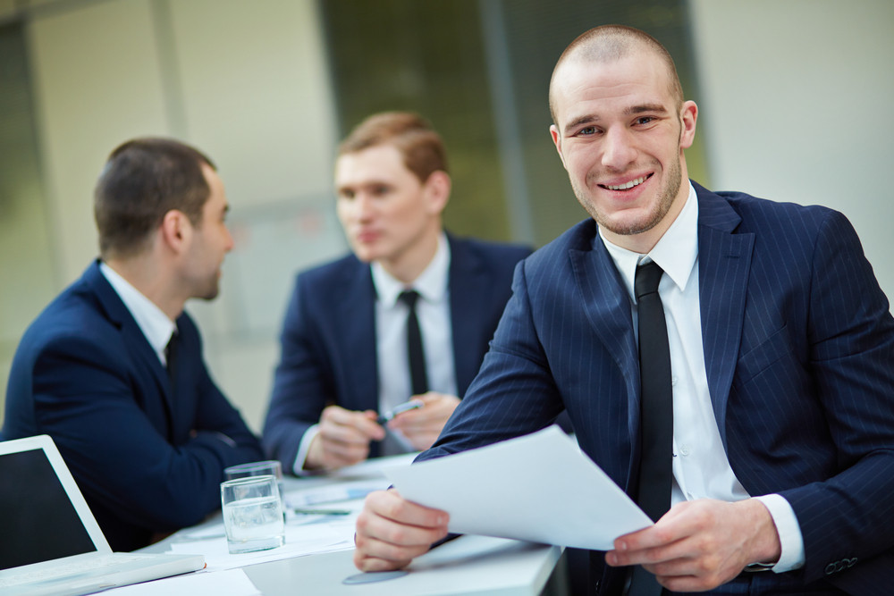 Young Businessman With Document Looking At Camera In Working Environment
