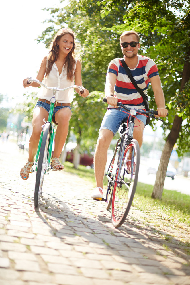 Portrait Of Happy Girl And Guy Cycling In Park At Leisure