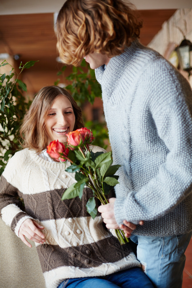 A Young Man Giving Bunch Of Red Roses To His Girlfriend