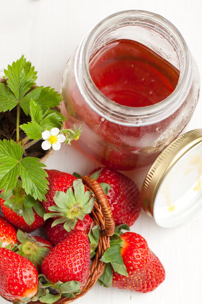 Basker Of Fresh Strawberries And Pot Of Honey