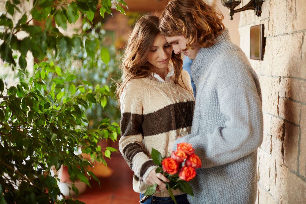 A Young Man And His Girlfriend With Red Roses In Cafe