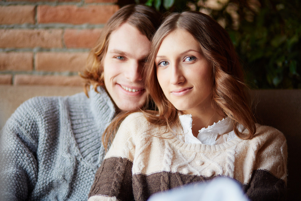 Portrait Of Amorous Young Couple Looking At Camera With Smiles
