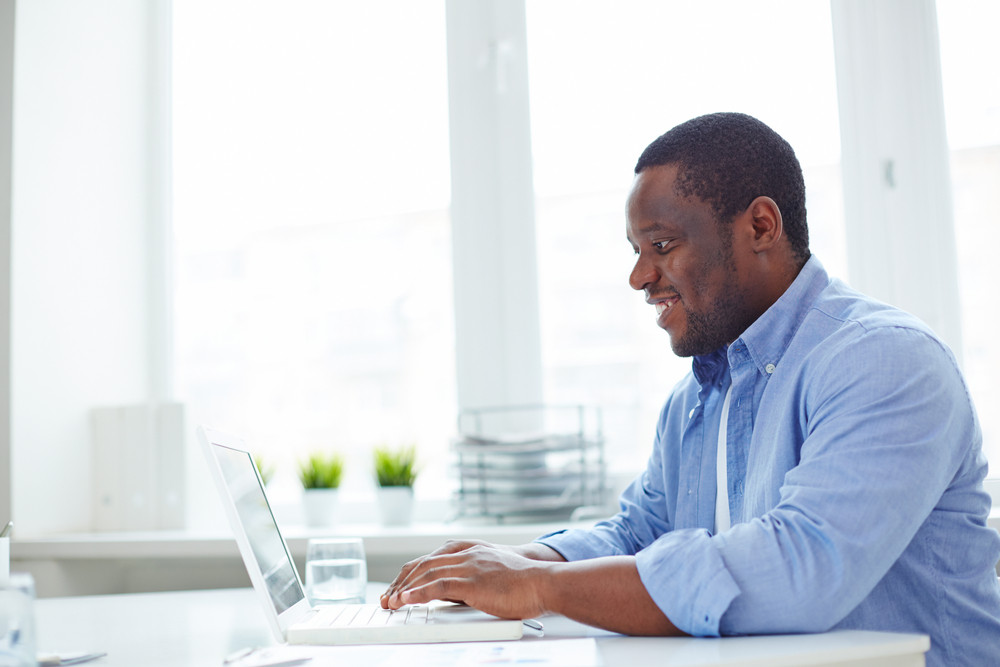 African-american Businessman Typing On Laptop In Office