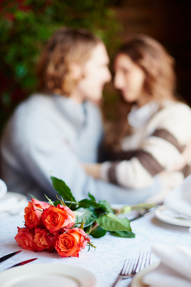 A Bunch Of Red Roses On Served Table And Young Lovers Embracing On Background