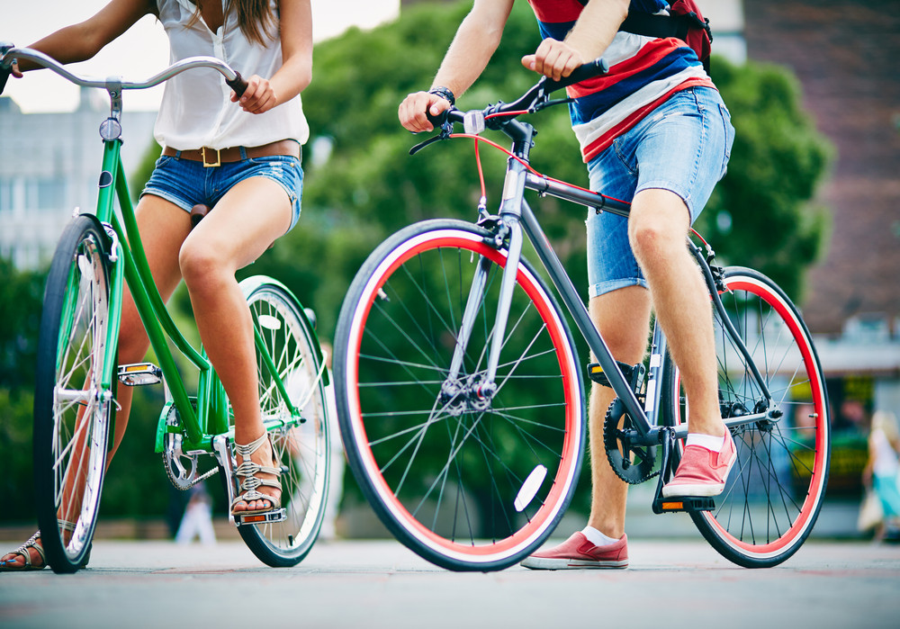 Close-up Of Guy And Girl Legs With Bicycles In The Park