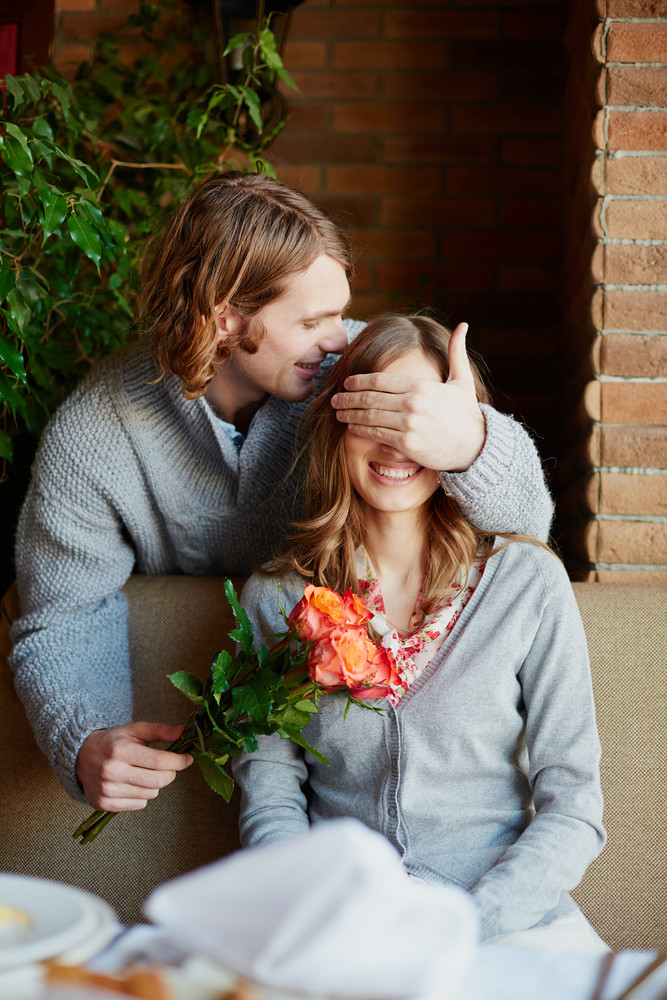 A Young Man Giving Bunch Of Red Roses To His Girlfriend While Closing Her Eyes
