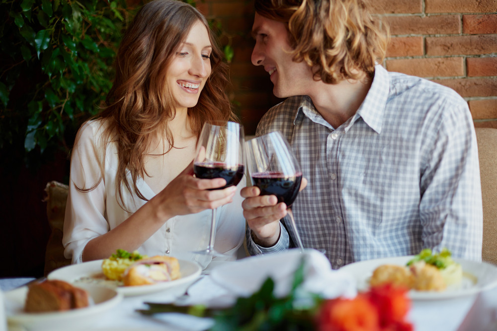 Portrait Of Amorous Young Couple Toasting With Red Wine