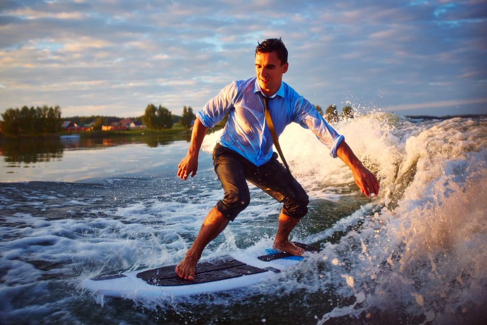 Active Young Man Surfboarding At Summer Resort