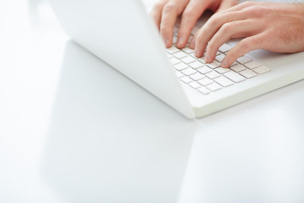 Fingers Of Businessman Touching Laptop Keys