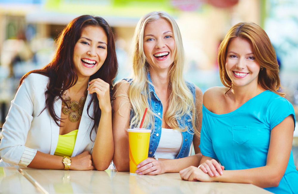 Portrait Of Three Happy Girls Looking At Camera While Having Drink After Shopping