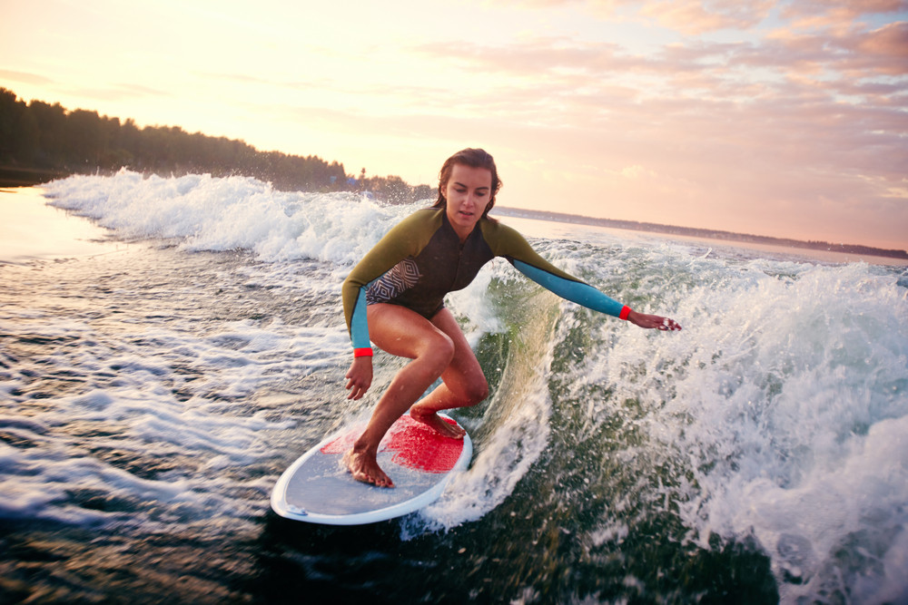 Pretty Girl Surfboarding In The Sea At Summer Resort