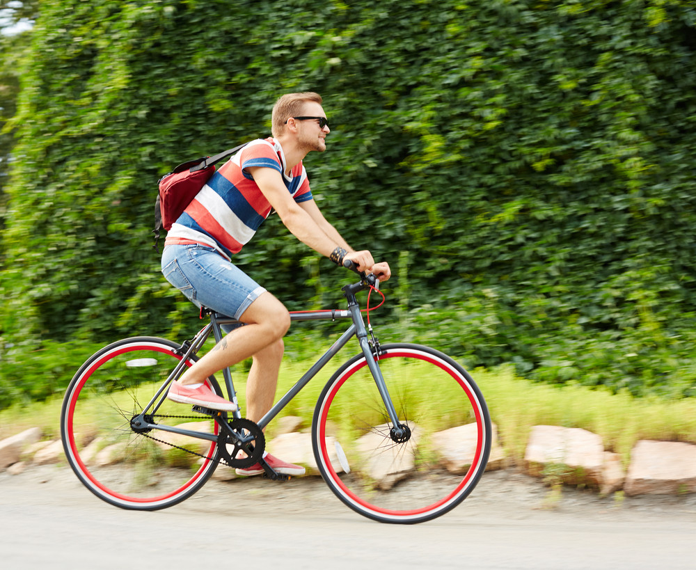 Portrait Of Handsome Guy Riding Bicycle In The Park