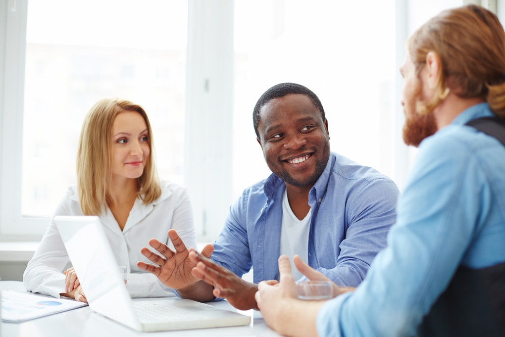 Group Of Co-workers In Casual Interacting At Business Meeting