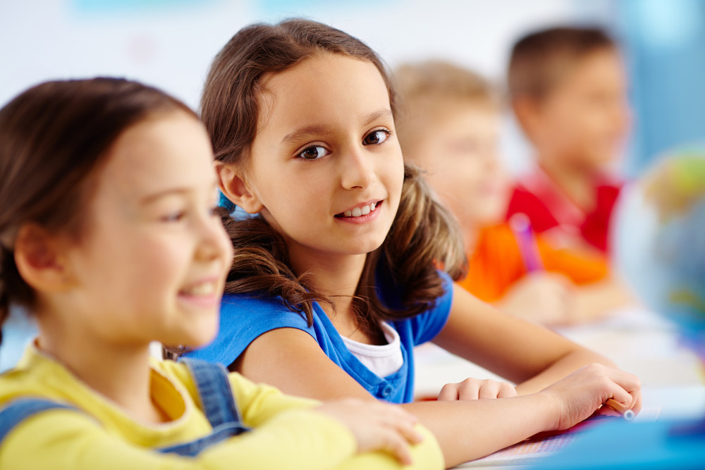 Portrait Of A Smiling Pupil Sitting Next To Her Classmate