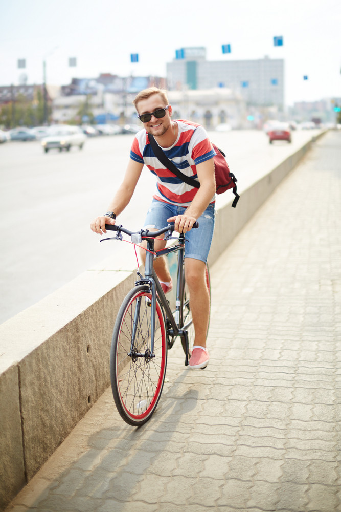 Portrait Of Happy Guy Riding Bicycle In The City