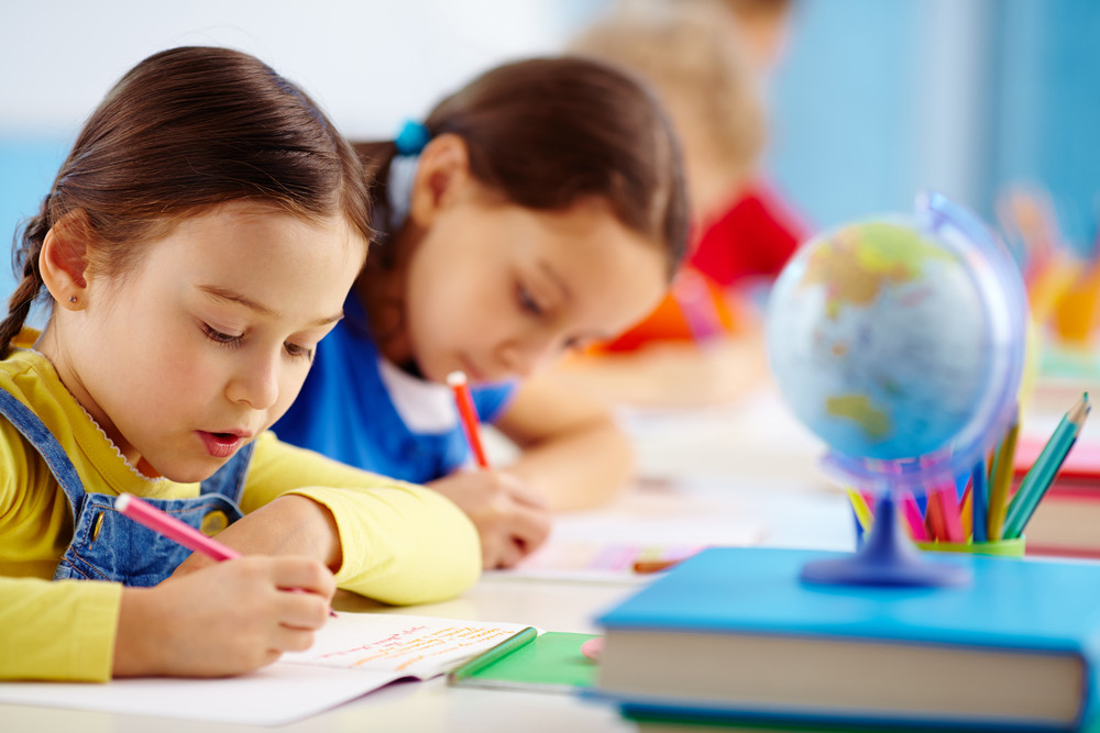 Pupils Sitting In A Row Writing A Test