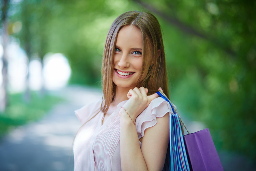 Portrait Of Happy Girl With Shopping Bags Looking At Camera Outdoors