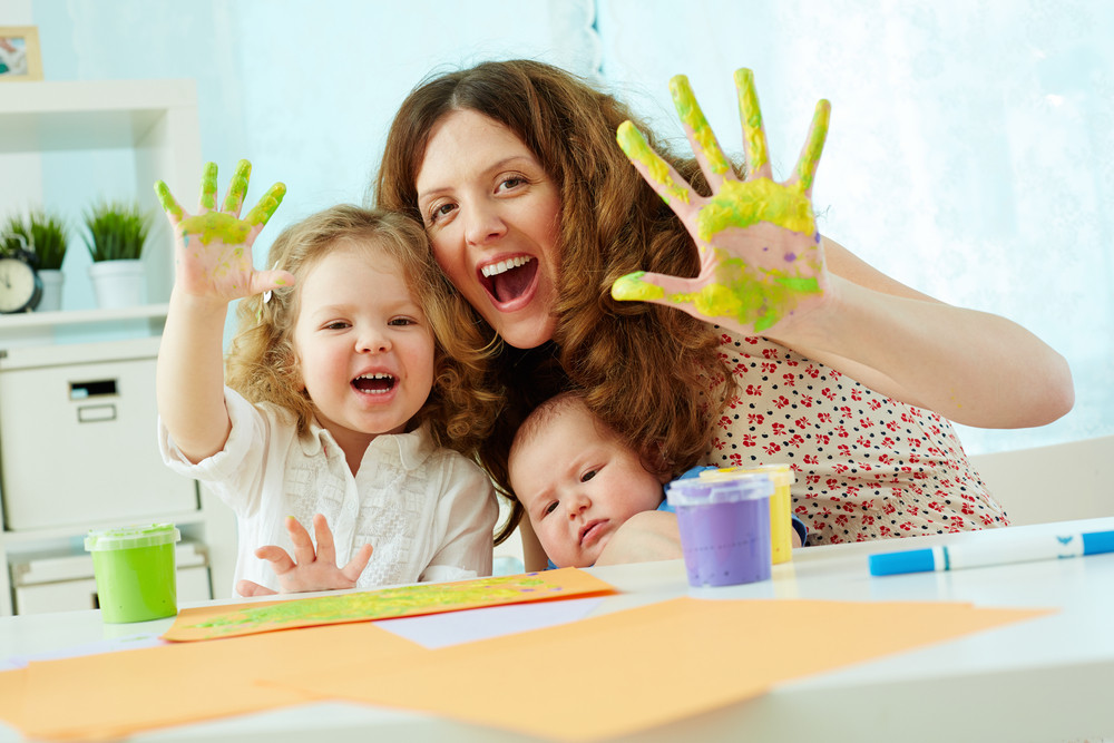 Portrait Of A Happy Family Having Fun Painting With Palms And Fingers