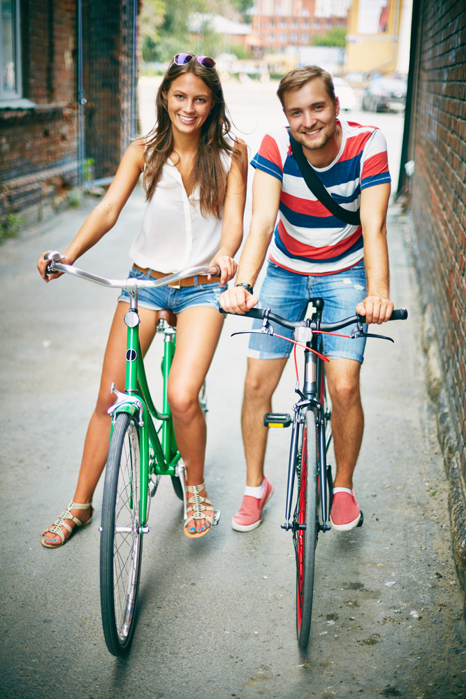 Portrait Of Happy Young Couple On Bicycles Looking At Camera