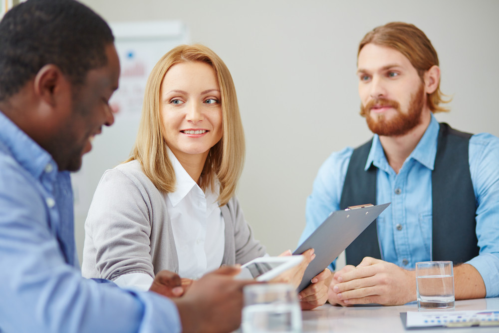 Attentive Businesswoman Looking At One Of Male Colleagues At Meeting