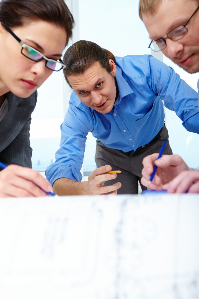 Three Businesspeople With Pencils Bending Over A Draft
