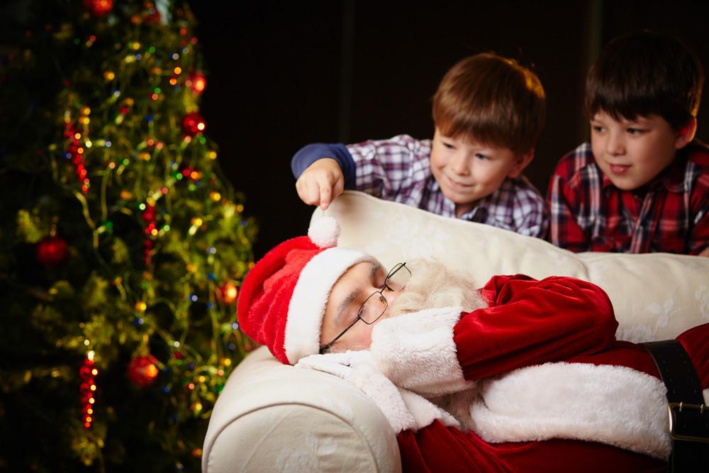 Cute Siblings Looking At Santa Claus Sleeping By Xmas Tree