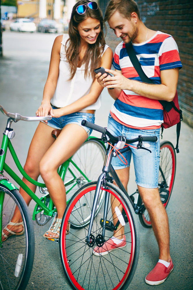 Portrait Of Happy Young Couple Of Bicyclists Using Cellphone In The Street
