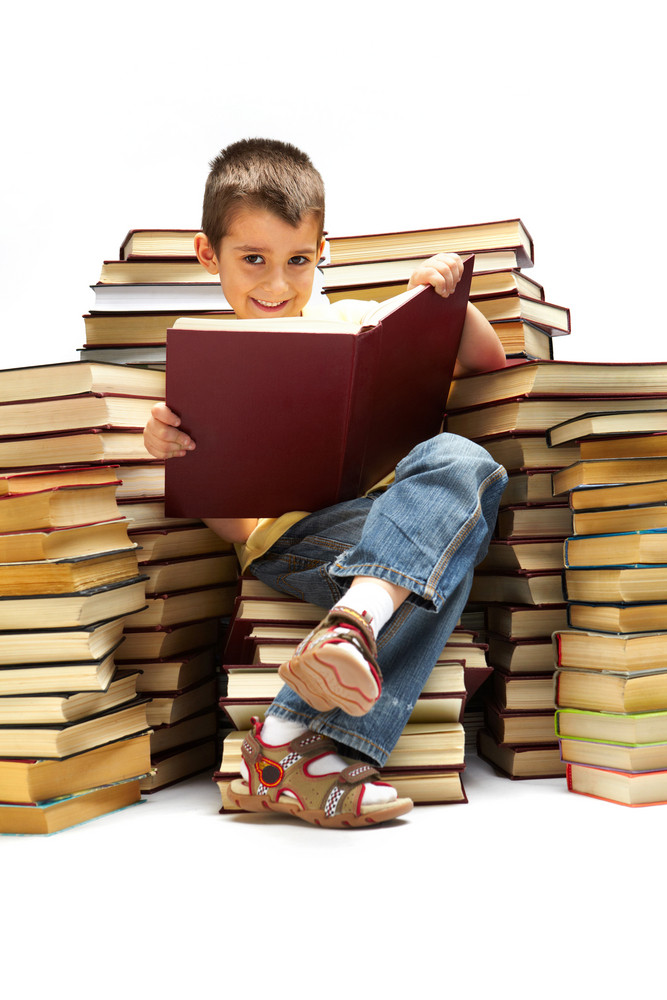 Photo Of Young Boy Looking At Camera While Reading A Book