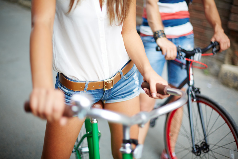 Close-up Of Young Woman With Bicycle On Background Of Her Friend