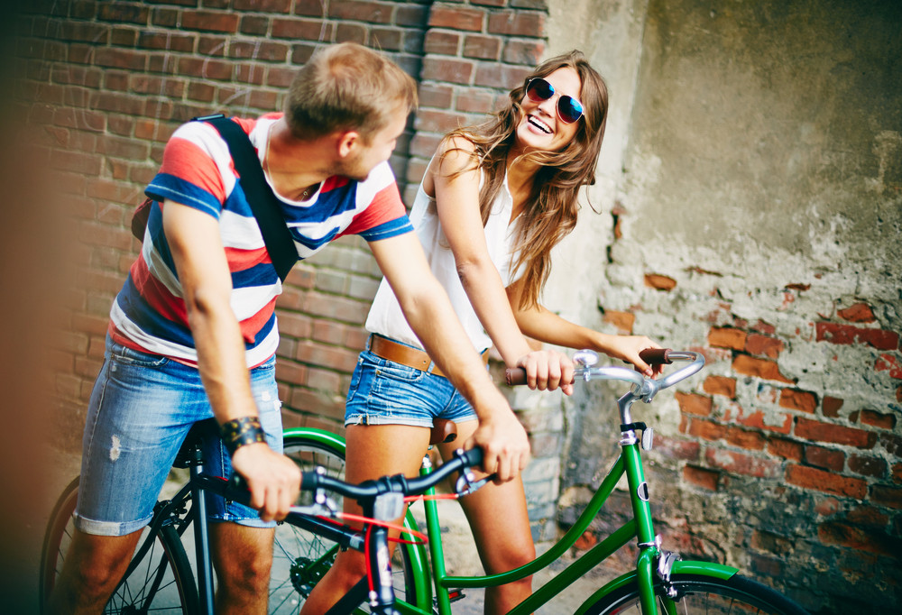Portrait Of Happy Young Couple Riding On Bicycles And Chatting