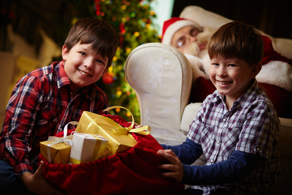 Happy Boys With Sack Full Of Presents Looking At Camera With Sleeping Santa Claus On Background