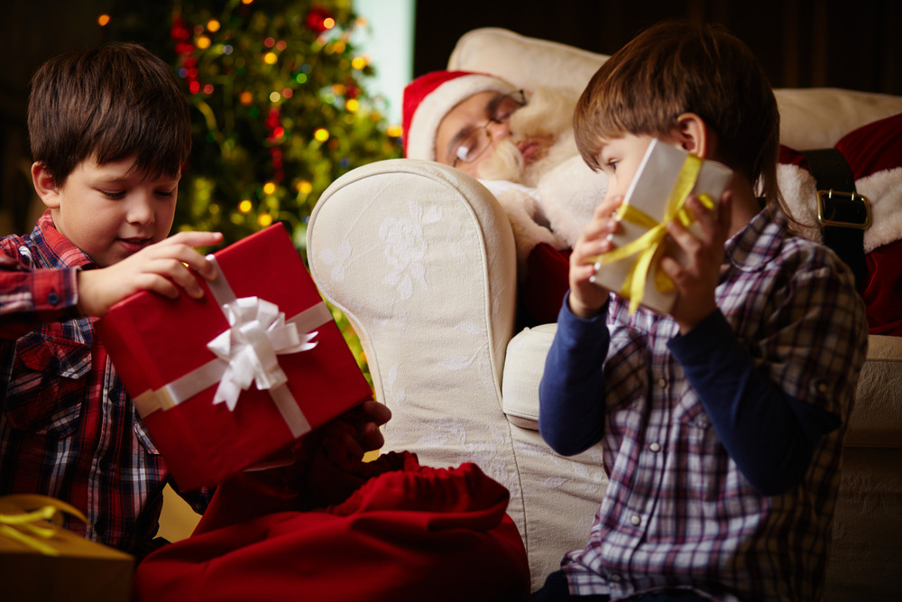Two Brothers Choosing Gifts From Sack With Santa Claus Sleeping On Background
