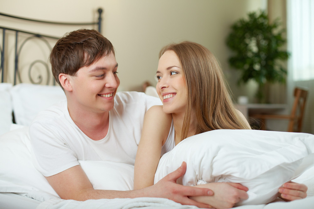 Happy Young Couple Lying In Bed And Looking At One Another