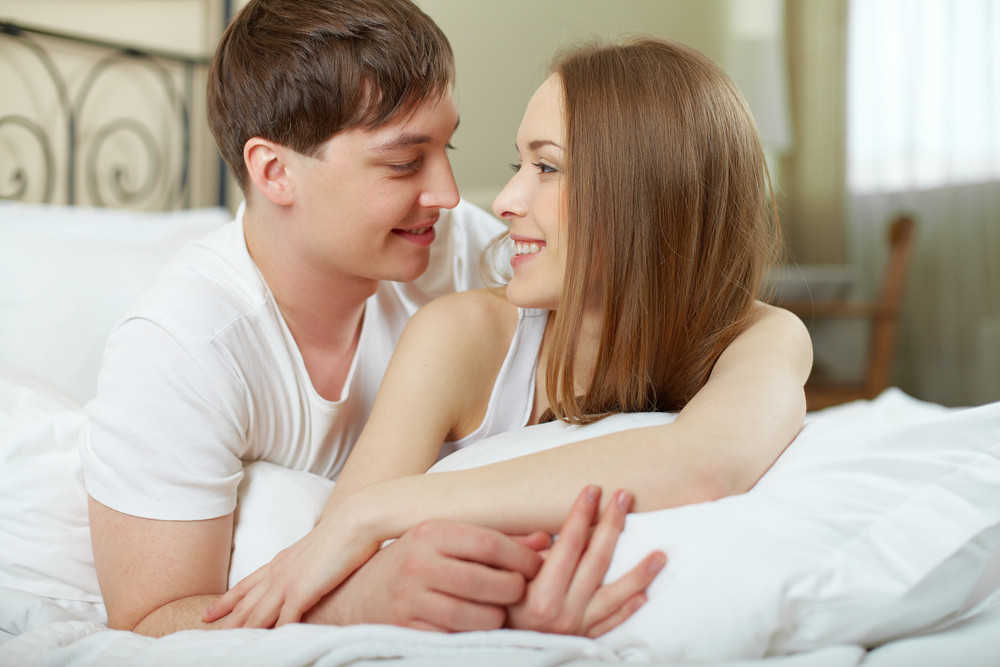 Romantic Couple Lying In Bed And Looking At One Another
