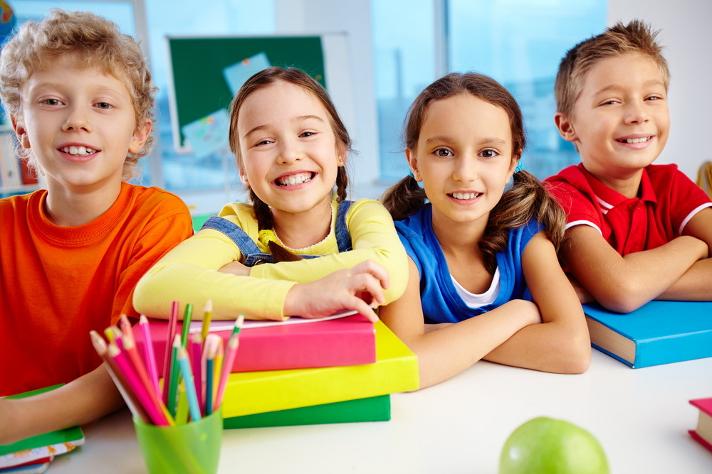 Portrait Of Cheerful School Children Flashing Toothy Smiles