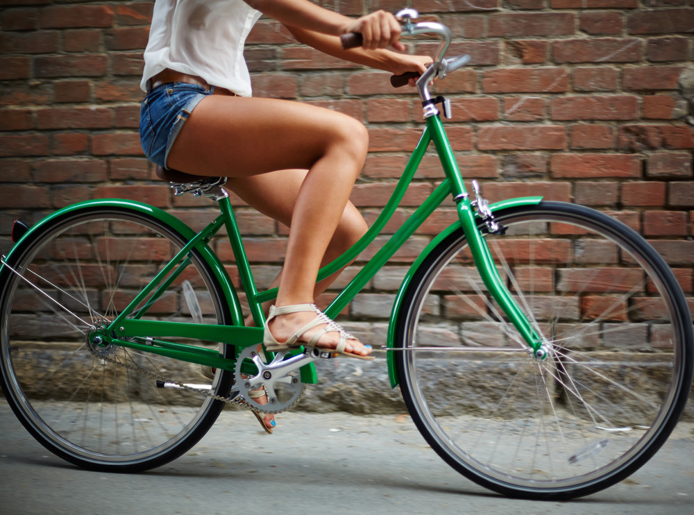 Close-up Of Young Woman Riding Bicycle Against Brick Wall