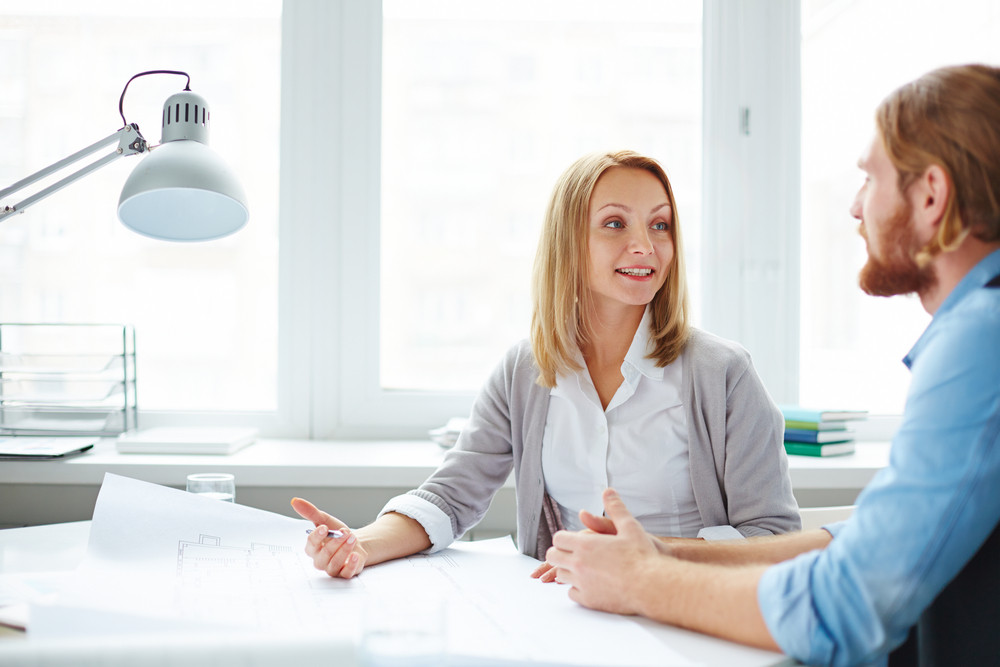 Female Designer Explaining Her Ideas To Her Colleague At Meeting